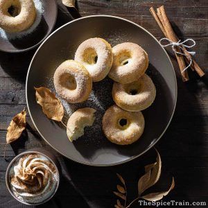 Baked sugar-coated donuts on a large plate with a cup of hot chocolate.