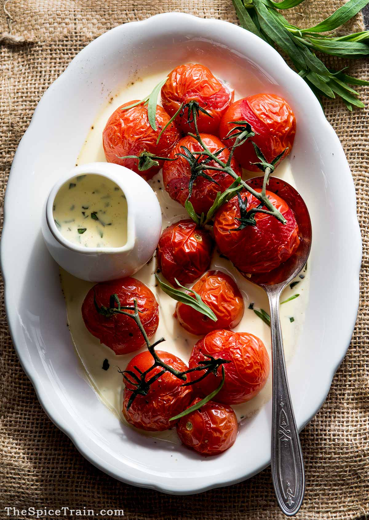 A serving plate with roasted tomatoes and tarragon cream sauce.