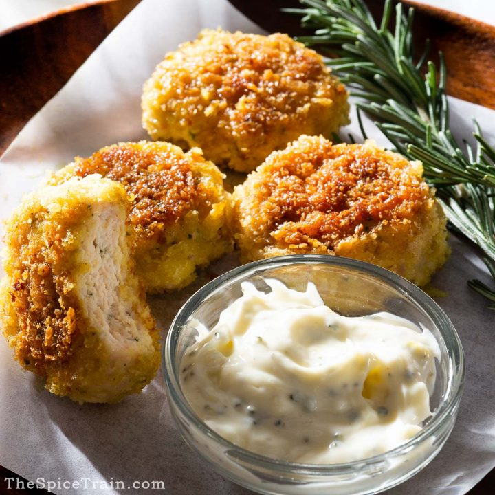 Chicken nuggets with aioli on a plate.