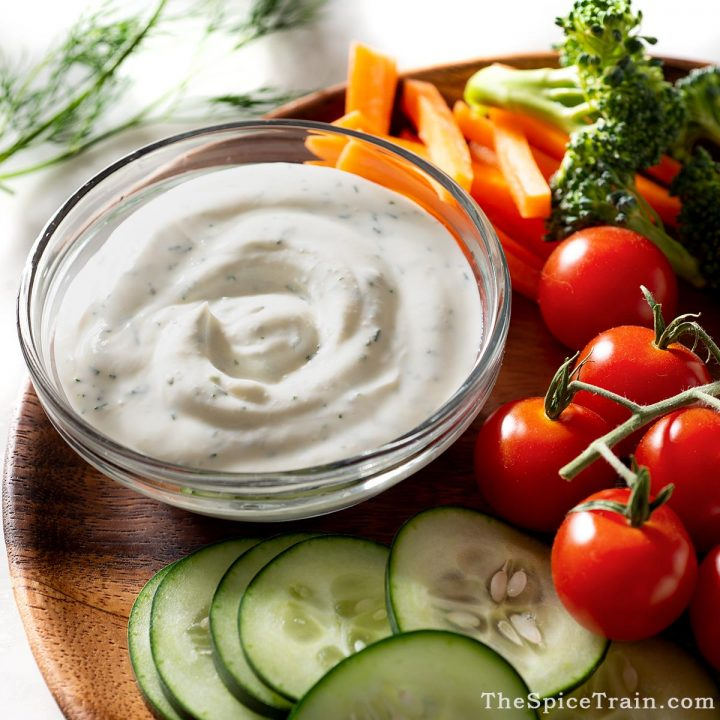 Raw vegetables on a plate with dip in a bowl.
