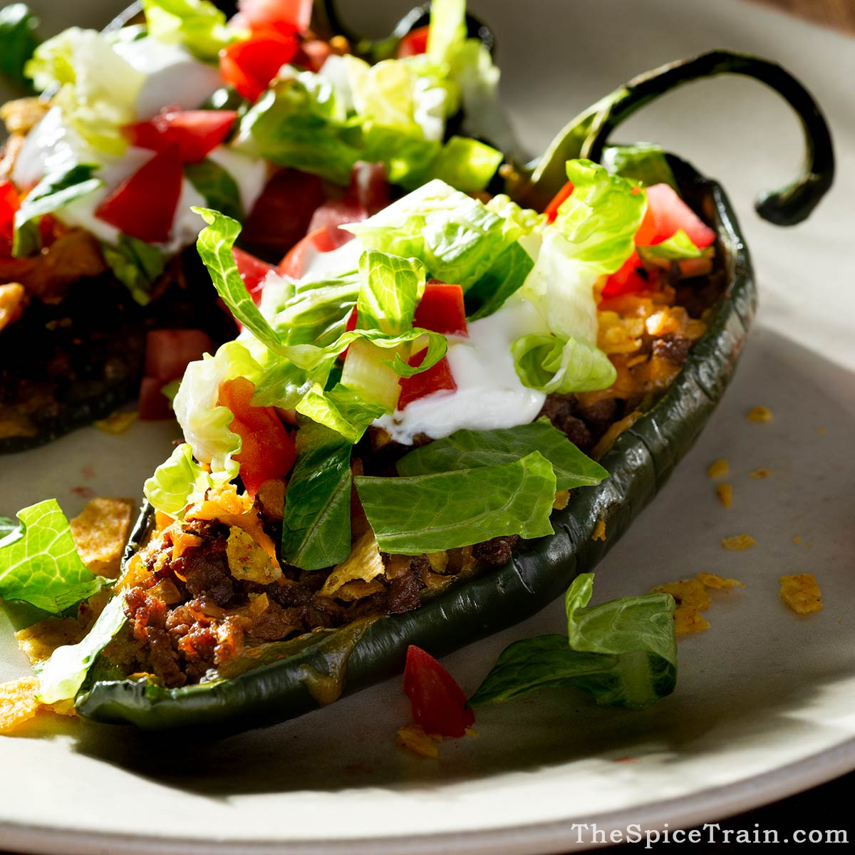 Stuffed poblano peppers with lettuce, tomato and sour cream topping.