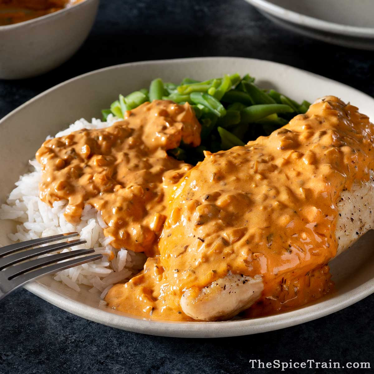 Chicken breast covered in chipotle sauce with rice and green beans.