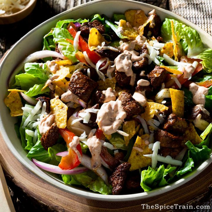 A steak salad with dressing in a bowl.