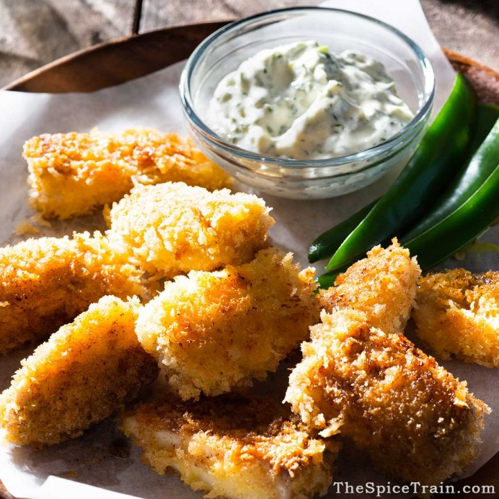 Breaded and fried fish bites with dipping sauce in a bowl.