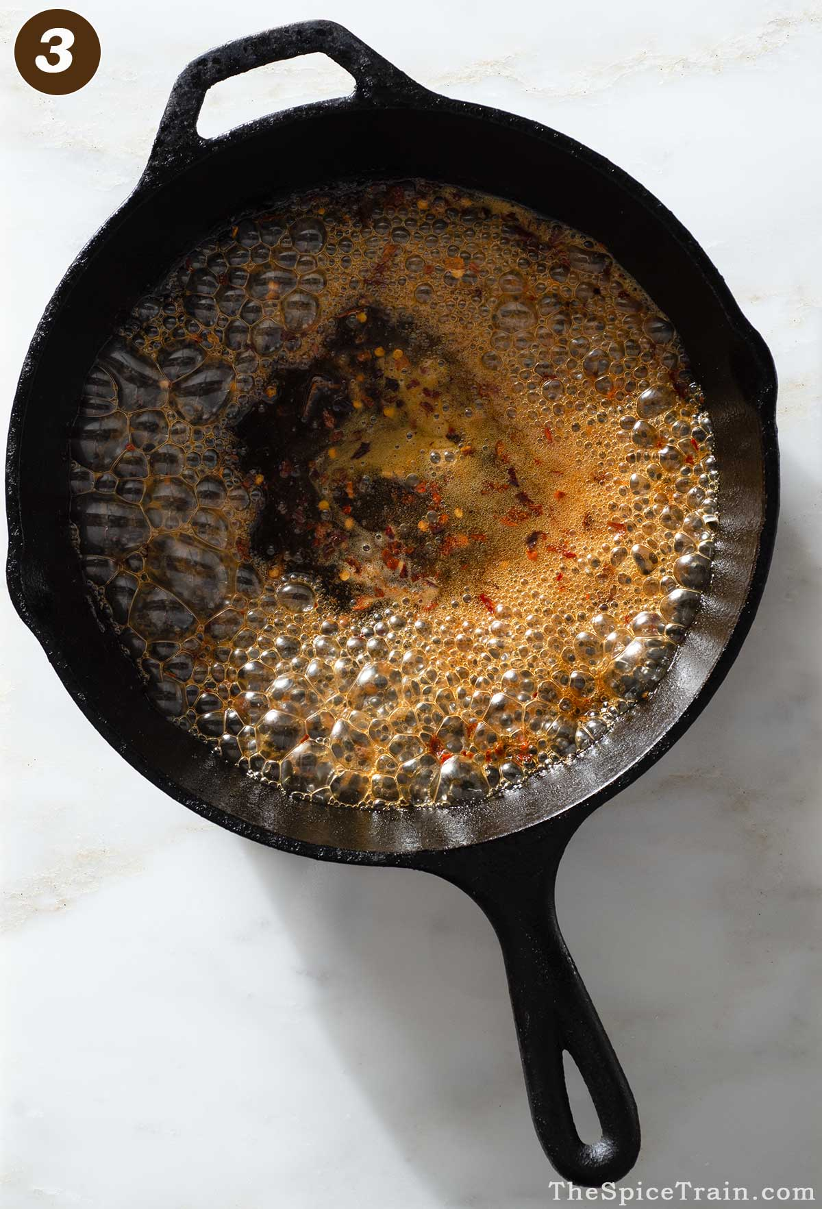 Bubbling sauce being cooked in a cast iron pan.