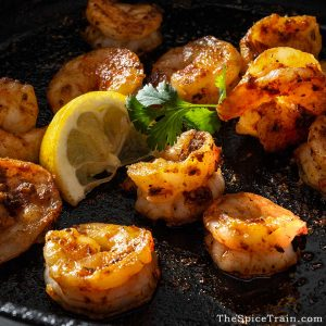 Cooked shrimp in a cast iron pan with a lemon wedge and cilantro.