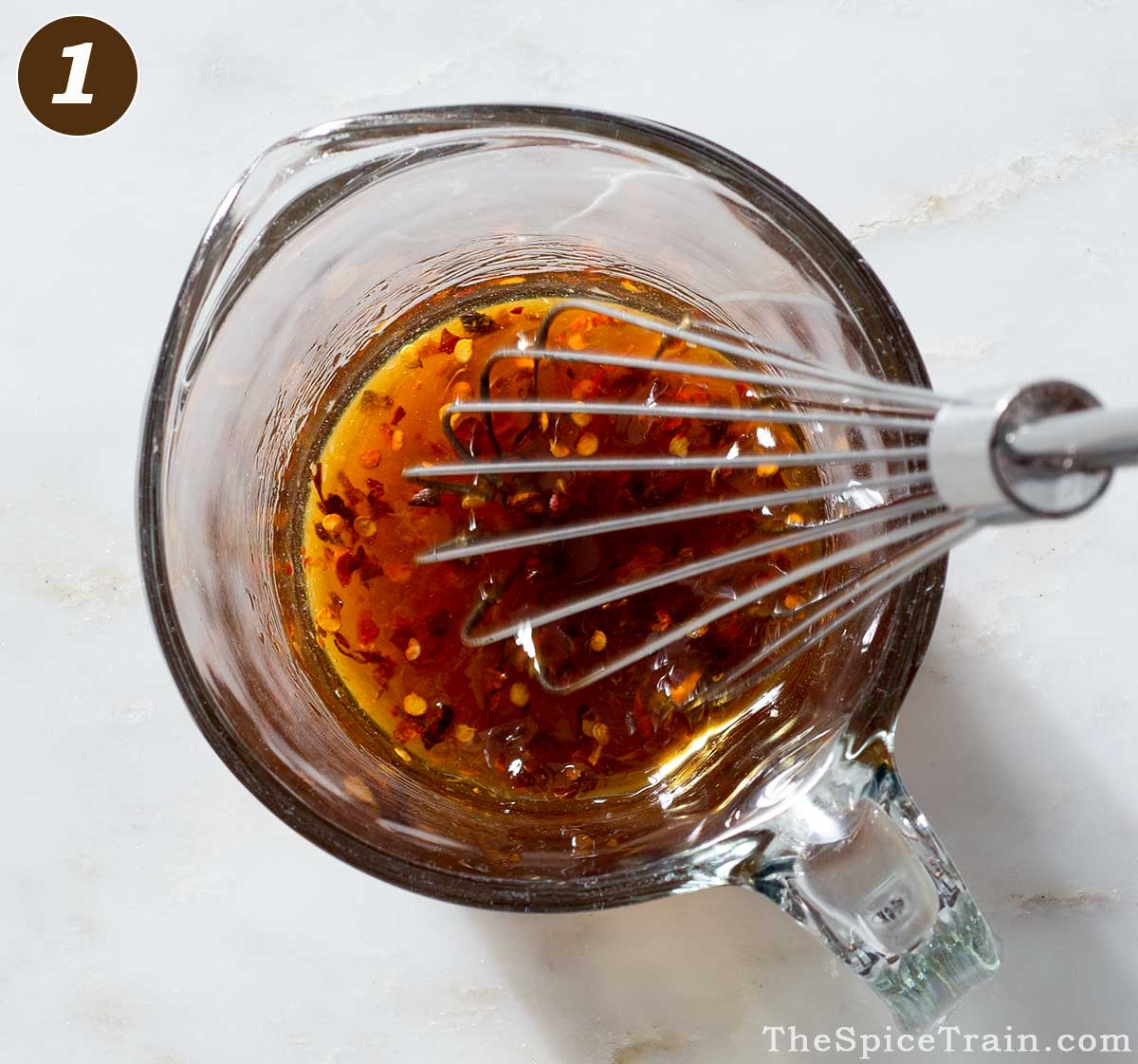 Sauce ingredients being whisked in a liquid measuring cup.