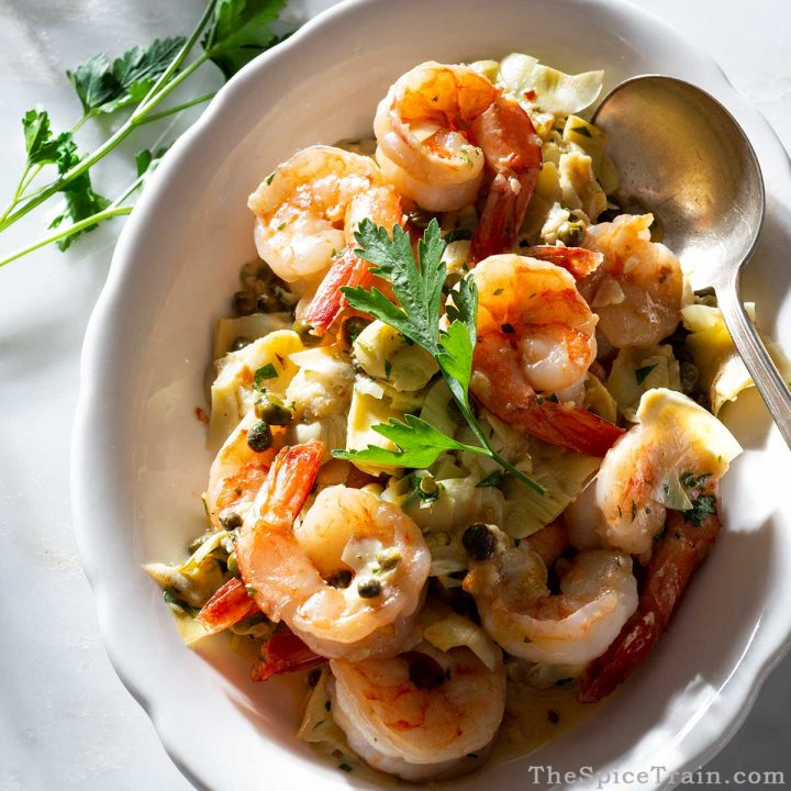 Shrimp with caper and artichoke sauce on a plate.
