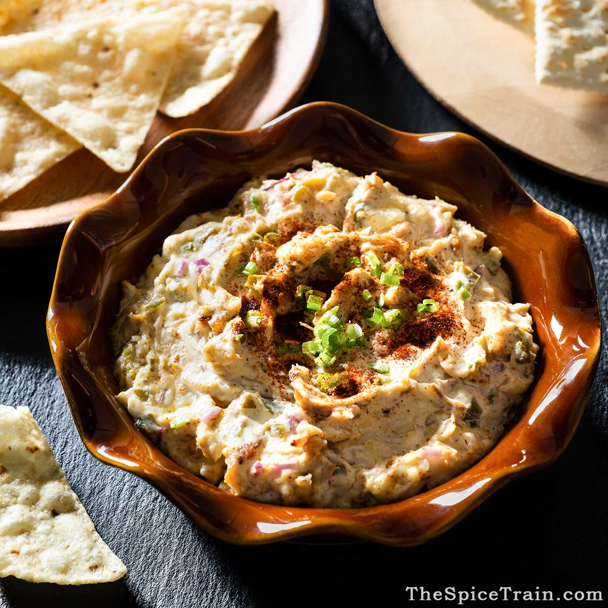 Chicken dip in a pie pan with tortilla chips and crackers.